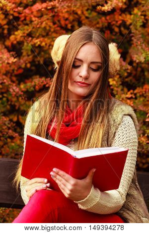 Woman Relaxing In Autumnal Park Reading Book
