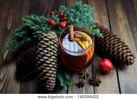 mulled wine with a lemon and cinnamon, red apple and cones