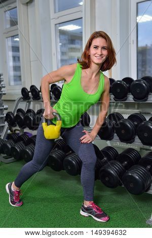 Fitness, sport, exercising lifestyle - middle age woman doing exercises with dumbbell at gym on broadest muscle of back.