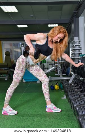 Fitness, sport, exercising lifestyle - Young woman doing heavy weight exercise for broadest muscle of back with dumbbells at gym.