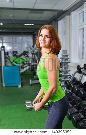 fitness, sport, training and lifestyle concept - middle aged woman doing exercises with dumbbells at gym .