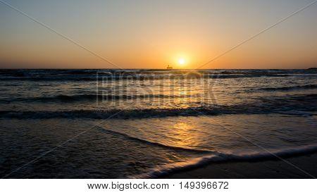 the sun rises over the horizon of the sea
