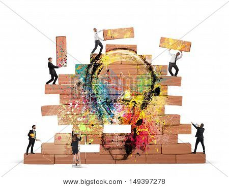 Business person built together a big brick wall with drawn lightbulb
