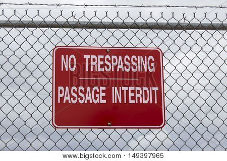 horizontal image of a big red sign saying No Trespassing in english and french language posted on a chain link wire fence with a cloudy sky in background with copy space.