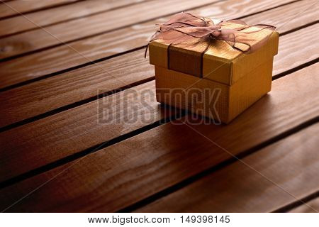Golden Gift Box On Diagonal Table Wooden Slats Elevated View
