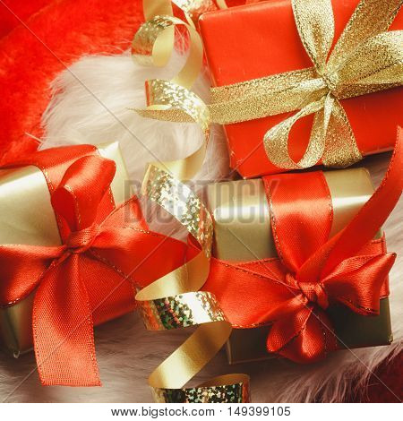 Holidays present christmas concept. Small boxes with gifts tied bows on red background