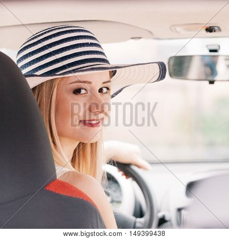 Summer road trip travel freedom concept. Pretty woman sit in car indoor keeps wheel smiling attractive blonde female ready for the journey on holidays