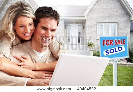 Couple with laptop near new house.
