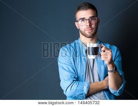 Portrait of a handsome young man standing and holding a cup of coffee in his hands