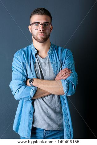 Portrait of a happy casual man standing isolated on a dark background