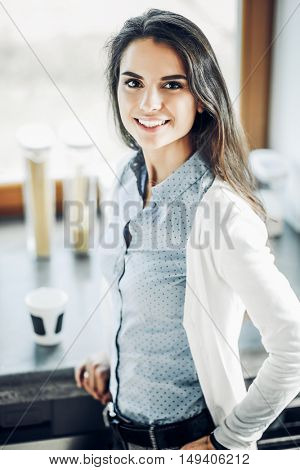 Young woman is standing near window