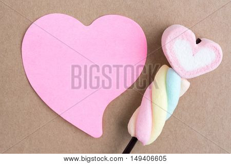 valentine candy with blank hearts note paper on brown background for season greeting