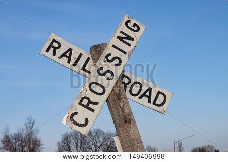 White Railroad Crossing Sign Against Blue Sky