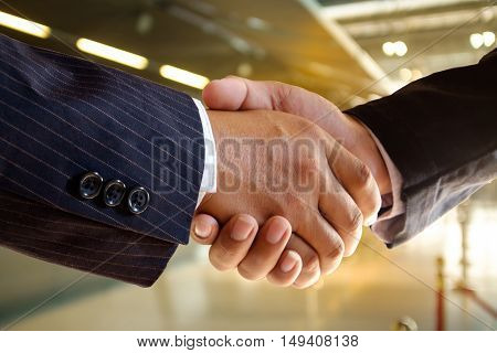 Shot of businessmen handshaking in terminal airport background. Acquisition concept.