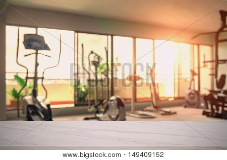 Empty wooden top marble and fitness Gym blurred background. For product display.
