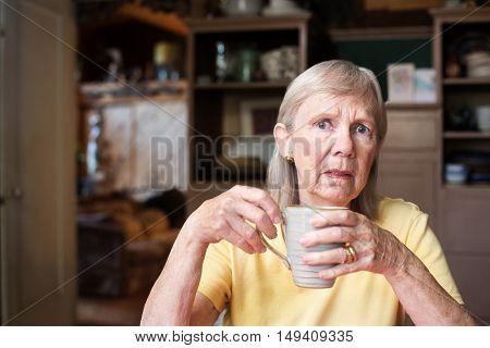 Worried Senior Woman Holding Coffee Cup