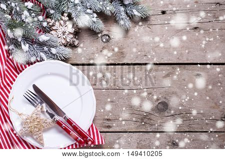 White plate knife and fork napkin and christmas decorations in white and red colors on aged table. Top view. Place for text. Selective focus. Drawn snow.