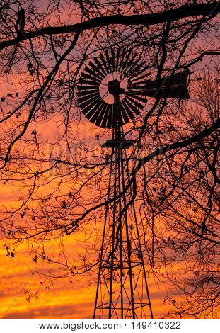 the silhouette of a windmill with a brillant sunset.