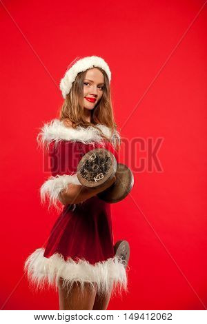 christmas, x-mas, winter, happiness concept - Bodybuilding. Strong fit woman exercising with dumbbells in santa helper hat , over red background. Muscular blonde girl lifting weights studio shot.