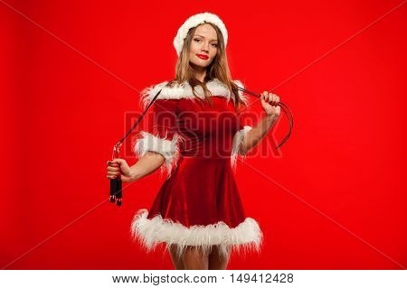 christmas, x-mas, winter, happiness concept - Sport, activity. Cute woman with skipping rope  in santa helper hat , over red background