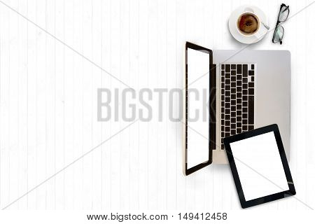 Top view of white office desk with laptopcup of coffee and supplies. Top view with copy space.