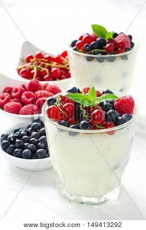 Sweet dessert, pudding, panna cotta with mix berries and mint, on white background