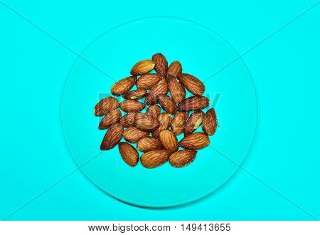 Almond in turquoise bowl on sweet colored background