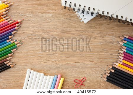 colorful stationary with pencils and a notebook