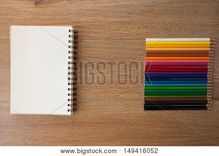 color pencils with notebook on a wooden table