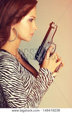 Beautiful woman holding hand gun