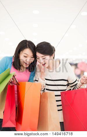 Happy friends - woman shopping in the mall shot in hong kong asian