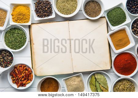 Blank cookbook and various spices and herbs. Top view.