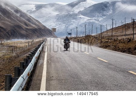 Biker motorcycle on the road beautiful winter in Tibet under snow mountain Sichuan China