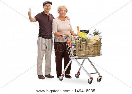 Full length portrait of an elderly couple posing with a shopping cart and giving a thumb up isolated on white background