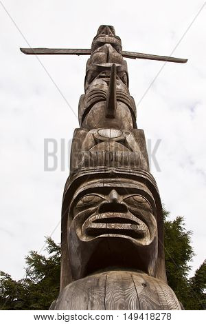 Vertical single carved wood Totem Pole looking from the ground to the cloudy sky in Stanley Park. They are located on the eastern point, just before Hallelujah Point on a bright, sunny spring day.