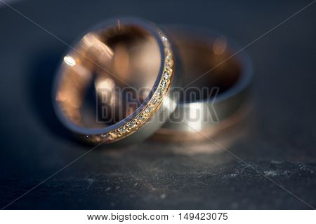 Wedding day details - two lovely golden wedding rings awaiting their moment (shallow DOF; color toned image)