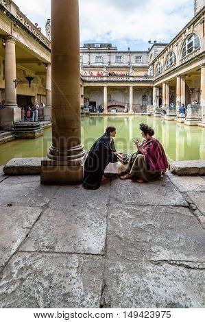 Bath UK - August 15 2015: Actors playing the role of old roman citizens. The Roman Terms complex is a site of historical interest in the English city of Bath. The Baths are a major tourist attraction