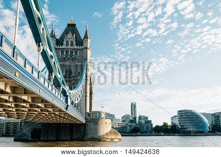 LONDON UK - AUGUST 21 2015: Tower Bridge and City Hall in London UK. The bridge crosses the River Thames close to the Tower of London and has become an iconic symbol of London