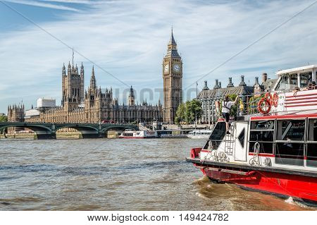 LONDON UK - AUGUST 22 2015: The Big Ben the Houses of Parliament and Westminster Bridge in London with a red tourist boat on the foreground
