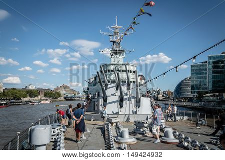 LONDON UK - AUGUST 22 2015: Tourist on the deck of the HMS Belfast in London a sunny day with blue sky