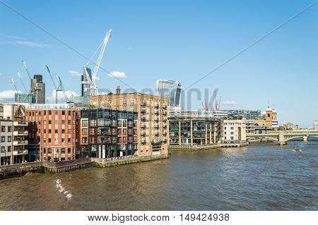 LONDON UK - AUGUST 22 2015: London riverside from Millennium Bridge. Regeneration area with construction cranes