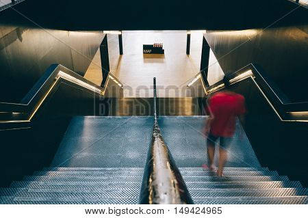 LONDON UK - AUGUST 22 2015: High angle view of stairs in Tate Modern Art Gallery interior. A blurred young is going down