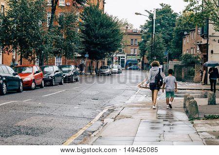 LONDON UK - AUGUST 23 2015: People walking on Swanfield Street a rainy day. Swanfield street is located in Shoreditch near Brick Lane Market.