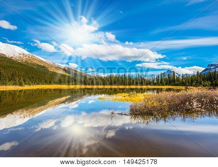 The sun is reflected in the smooth water of the lake. Rocky Mountains on a sunny autumn day. The concept of active tourism and ecotourism