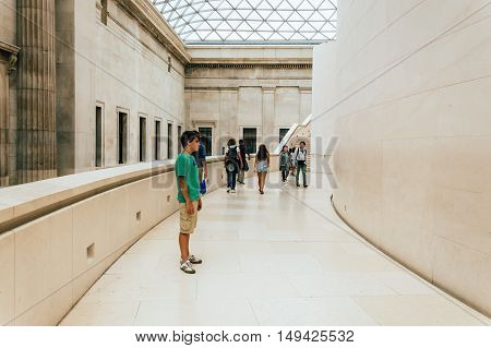 LONDON UK - AUGUST 20 2015: Young standing on British Museum main court stairs. The British Museum in London is dedicated to human history and culture.