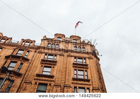 London UK - August 19 2015: Low angle view of Harrods Department Store with a union jack flag on top. Harrods is the most famous and luxury department store in the world.