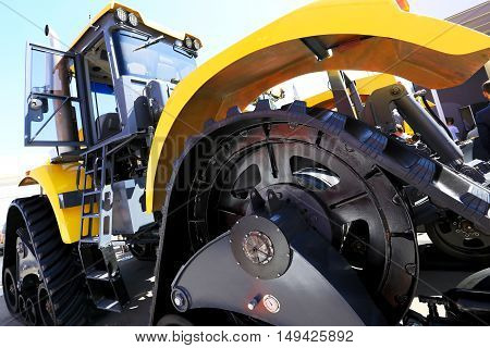 Big black wheel yellow construction truck with steps