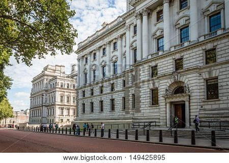 London UK - August 19 2015: Her Majesty's Treasury Building Government Offices in Horse Guard Road Westminster a csunny day with white clouds and people walking