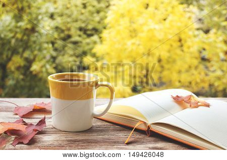 Cup of tea with notepad on the wood background