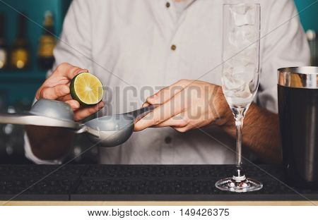 Barman's hands in bar interior making alcohol cocktail. Professional bartender at work in bar squeezing lime into mixing glass for citrus drink. Party time in night club